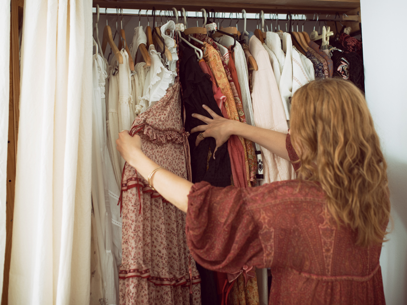 A woman selects clothes from her wardrobe