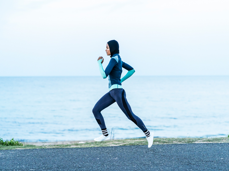 A woman wearing a hijab running by the sea